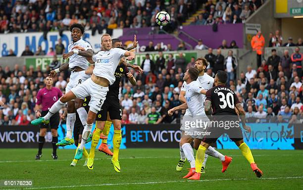 Swansea players Leroy Fer and Mike van der Hoorn compete against the Manchester City defence at a corner during the Premier League match between...