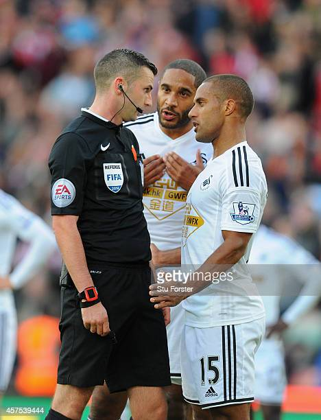 Swansea players Wayne Routledge and Ashley Williams confront referee Michael Oliver after Victor Moses had won a penalty during the Barclays Premier...