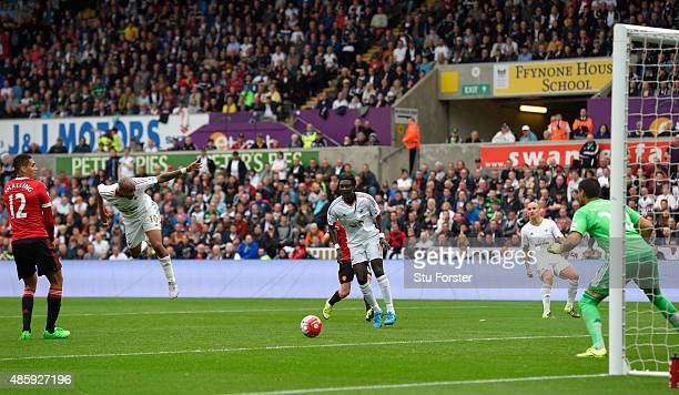 Swansea striker Andre Ayew heads the first swansea goal during the Barclays Premier League match between Swansea City and Manchester United on August...