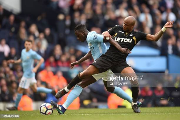 Swansea's Ghanaian strriker Andre Ayew vies with Manchester City's French defender Benjamin Mendy during the English Premier League football match...