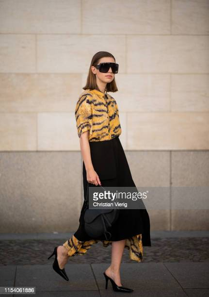 Swantje Sömmer is seen wearing button up dress with tiger print Hofmann Copenhagen black skirt with slit Aeron Dior sunglasses Dior saddle bag...