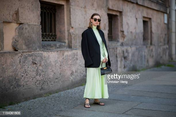 Swantje Sömmer is seen wearing neon pleated dress By Malene Birger black blazer Arket Zara sandals Tory Burch bag Tom Ford sunglasses on June 05 2019...