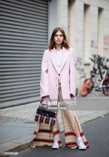Swantje Sömmer is seen wearing pink blazer Joseph wide leg pants with slit Zara JW Anderson x Converse chucks JW Anderson bag HM rip shirt on July 06...