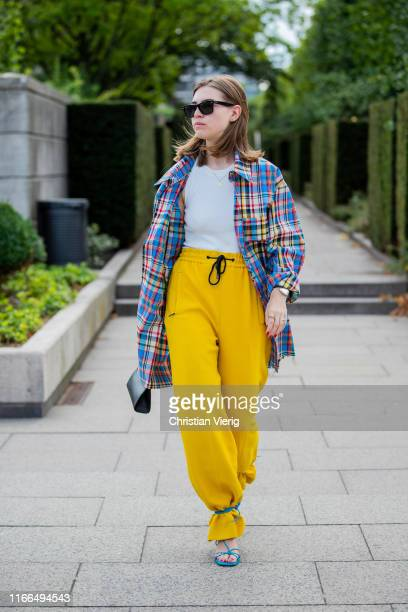 Swantje Sömmer is seen wearing plaid button shirt, yellow pants, Fendi bag, sandals outside Mykke Hofmann during Copenhagen Fashion Week...