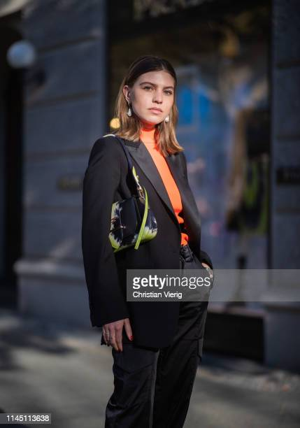 Swantje Sömmer is seen wearing Prada bag with jungle print black blazer pants orange top on April 25 2019 in Berlin Germany