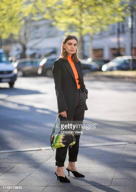 Swantje Sömmer is seen wearing Prada bag with jungle print black blazer pants orange top heels on April 25 2019 in Berlin Germany