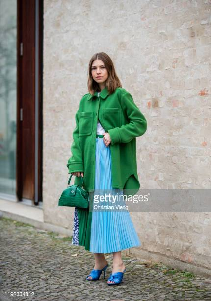 Swantje Sömmer is seen wearing shirt and green wool coat with pockets Arket, mulit colored mixed pattern pleated skirt in light blue and green...