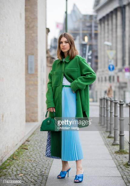 Swantje Sömmer is seen wearing shirt and green wool coat with pockets Arket mulit colored mixed pattern pleated skirt in light blue and green Lacoste...