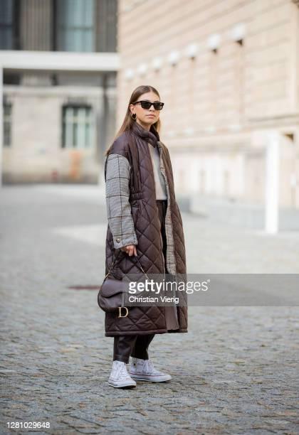 Swantje Soemmer is seen wearing brown coat with grey checkered sleeves Baum & Pferdgarten, black leather pants Zara, brown bag Dior, sunglasses...