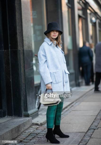 Swantje Soemmer is seen wearing bucket hat blue coat fake faux bag cropped green pants sock ankle boots outside Mykke Hofmann during the Copenhagen...