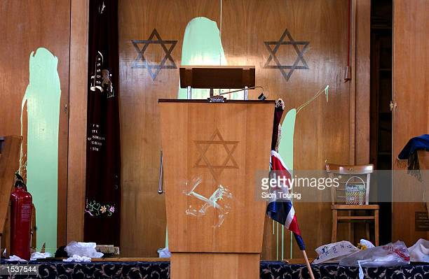 A swastika is daubed beneath the Star of David on a preaching lectern April 30 2002 at Finsbury Park Synagogue in London The synagogue was desecrated...