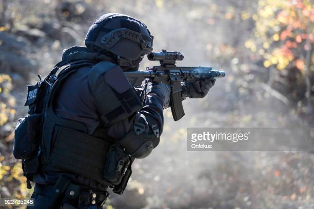 swat police officer shooting with firearm - armi foto e immagini stock