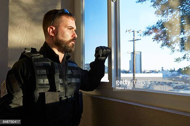 Swat team member looking out Window