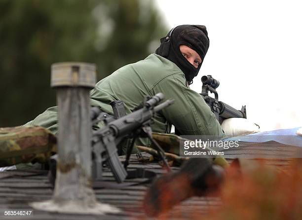 – A swat team sniper on the roof of a neighboring building looks over his shoulder during a five hour stand off A five–hour standoff at a Fullerton...