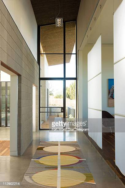 A swath of polished concrete leads from the entry to the east side of the home which is basically divided into four cubes flanked by a studio and...