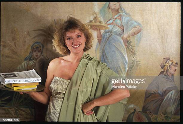 Swathed in Grecian robes Charlotte de Turckheim poses with her book Une Journee Chez Ma Mere mirroring the motif of the mural behind her
