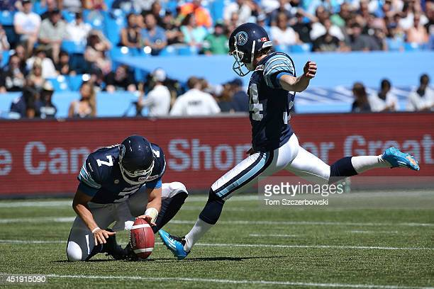 Swayze Waters of the Toronto Argonauts kicks a point after touchdown as Trevor Harris holds the ball during CFL game action against the Saskatchewan...