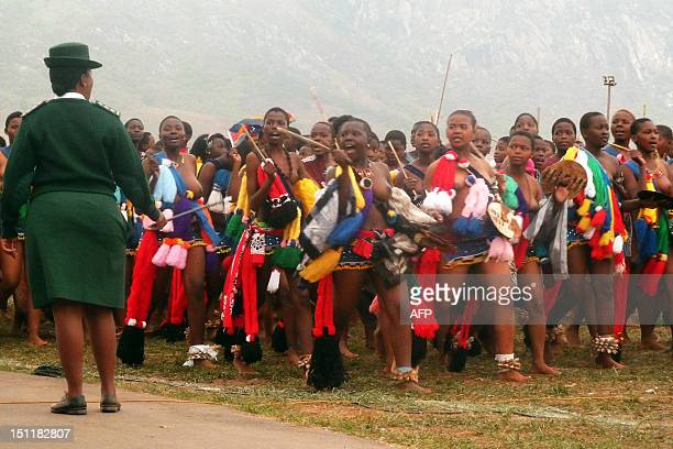 Swazi Correctional Services officer supervises Swazi girls performing on September 2 2012 the reed dance for King Mswati III at the Ludzidzini royal...
