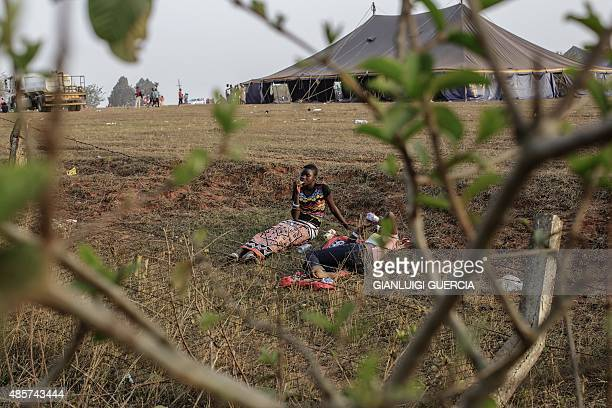 Swaziland girls rest and eat on a field by makeshift tents where thousands of them will sleep for the next two nights in the surroundings of the...