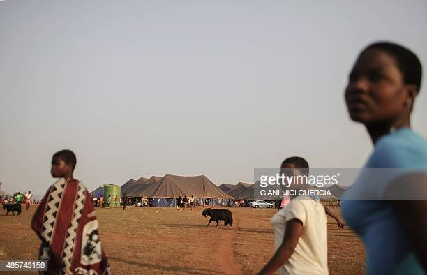 Swaziland girls walk through a field by makeshift tents where thousands of them will sleep for the next two nights in the surroundings of the...