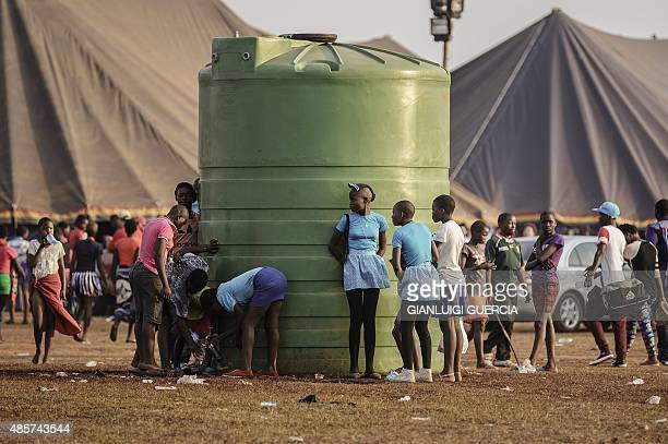 Swaziland's girls collect water from a tank on a field by makeshift tents where thousands of them will sleep for the next two nights in the...