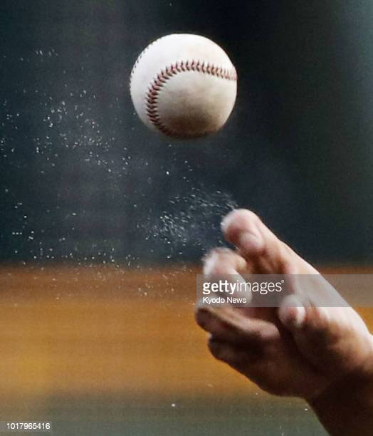 Sweat flies off as a pitcher throws the ball during a game at the 100th national high school baseball championship at Koshien Stadium in Nishinomiya,...