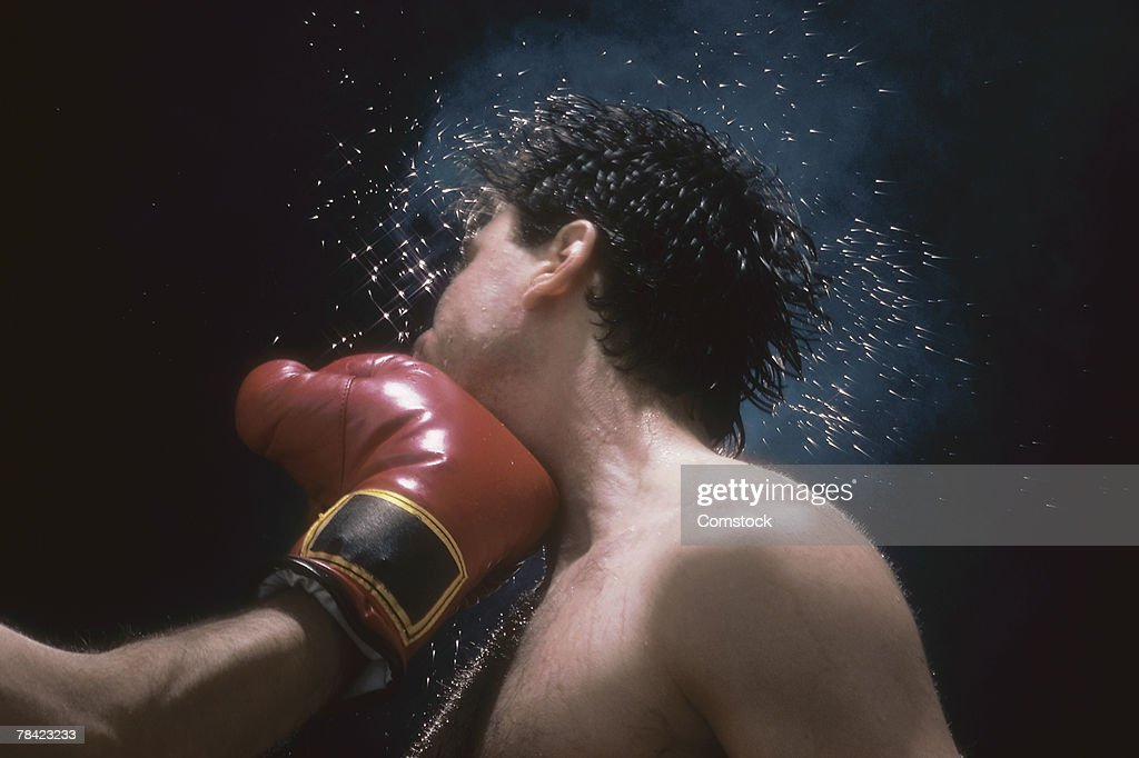 Sweat flying from boxer's head from force of punch : Stock Photo