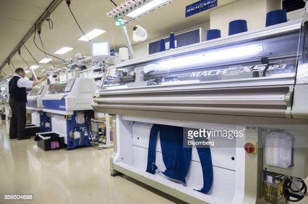 A sweater exits a wholegarment knitting machine inside the design center at the Shima Seiki Manufacturing Ltd headquarters in Wakayama Japan on...