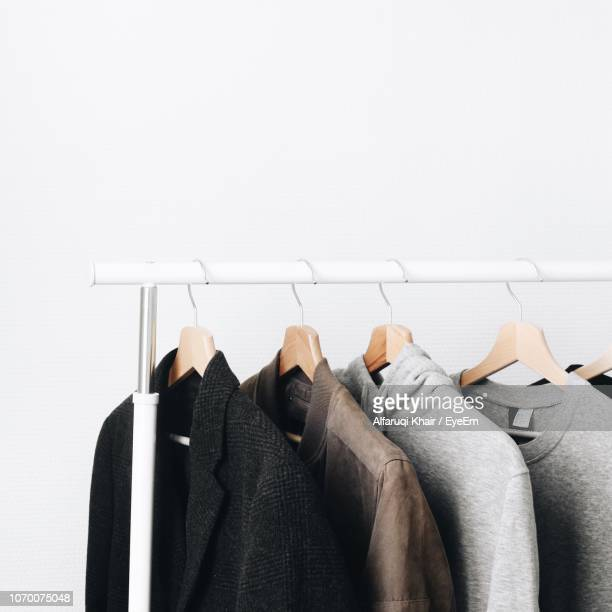 sweaters hanging on rack against wall - rack stock pictures, royalty-free photos & images