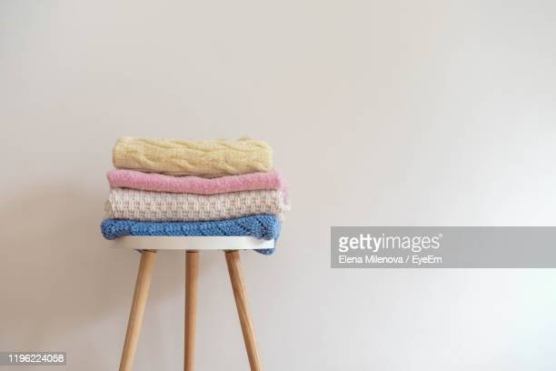 sweaters on table against white background - abiti pesanti foto e immagini stock