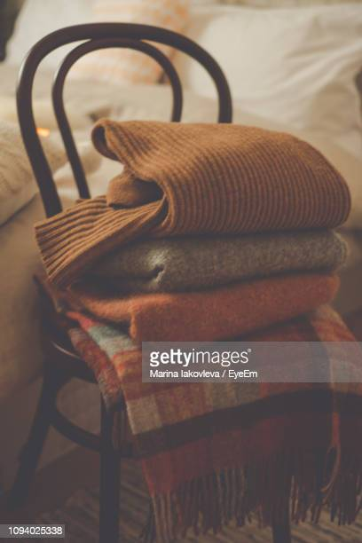 Sweaters Stacked On Chair In Bedroom