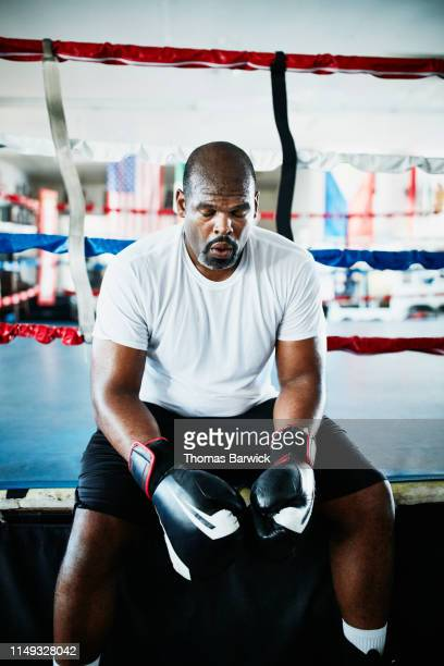 sweating male boxer with eyes close resting on edge of boxing ring during training session - boxing shorts stock pictures, royalty-free photos & images
