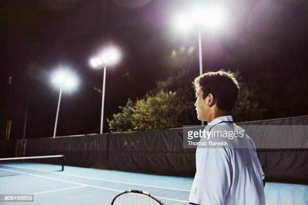 Sweating male tennis player waiting for service while playing on outdoor court at night