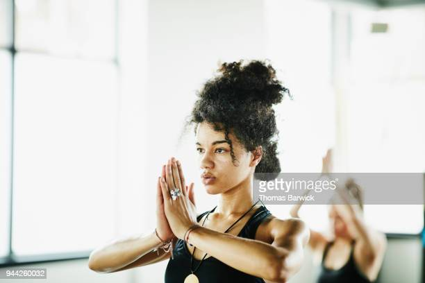 sweating woman in tree pose during hot yoga class in fitness studio - yoga stockfoto's en -beelden