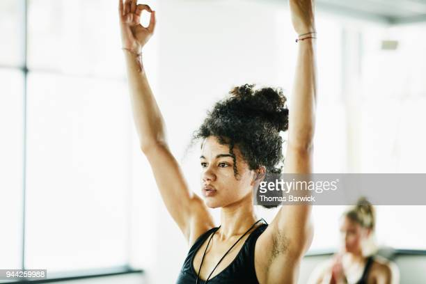 sweating woman in tree pose during hot yoga class - human limb stock pictures, royalty-free photos & images