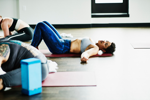 Sweating woman lying on yoga mat after hot yoga class in fitness studio - gettyimageskorea
