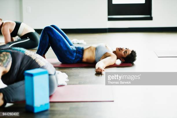 sweating woman lying on yoga mat after hot yoga class in fitness studio - lying on back stock pictures, royalty-free photos & images