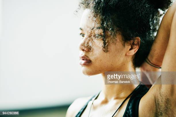 sweating woman stretching during hot yoga class - ナチュラルヘア ストックフォトと画像