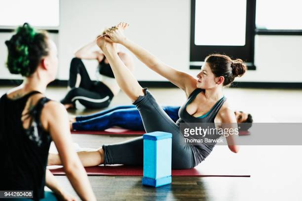 Sweating woman with one arm stretching after hot yoga class in fitness studio