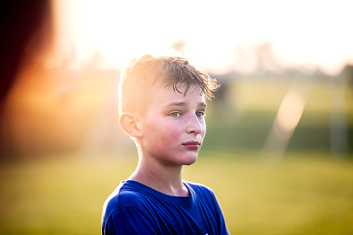 sweaty 11 year old boy watching teammates playing soccer from sidelines - gettyimageskorea