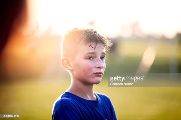 sweaty 11 year old boy watching teammates playing soccer from sidelines - 10 11 jaar stockfoto's en -beelden
