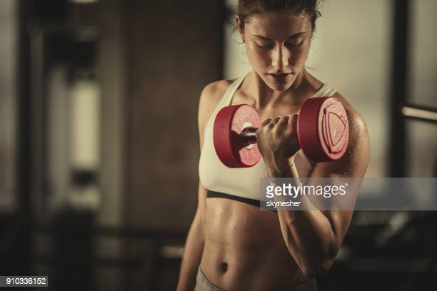 sweaty athletic woman exercising with dumbbells in a health club. - hand weight stock pictures, royalty-free photos & images