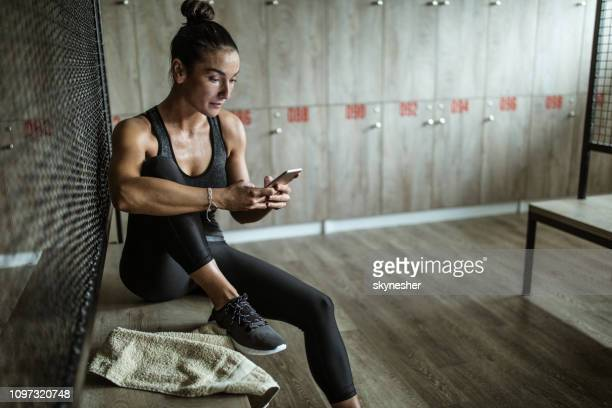 sweaty athletic woman using cell phone in locker room. - locker room stock pictures, royalty-free photos & images