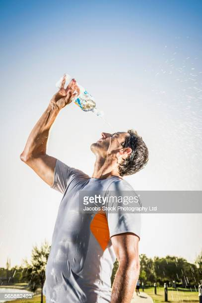 Sweaty Caucasian runner pouring water bottle on his face