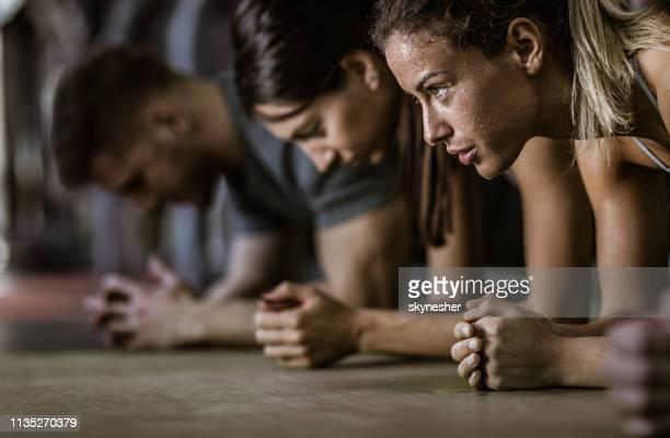 zweterige vrouwelijke atleet in een plank positie met haar vrienden in een sportschool. - uithoudingsvermogen stockfoto's en -beelden