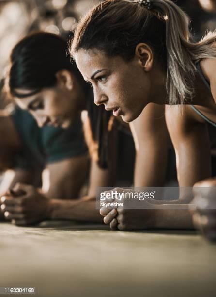 zweterige vrouwelijke atleet in een plankpositie met haar vrienden in een sportschool. - inspanning stockfoto's en -beelden