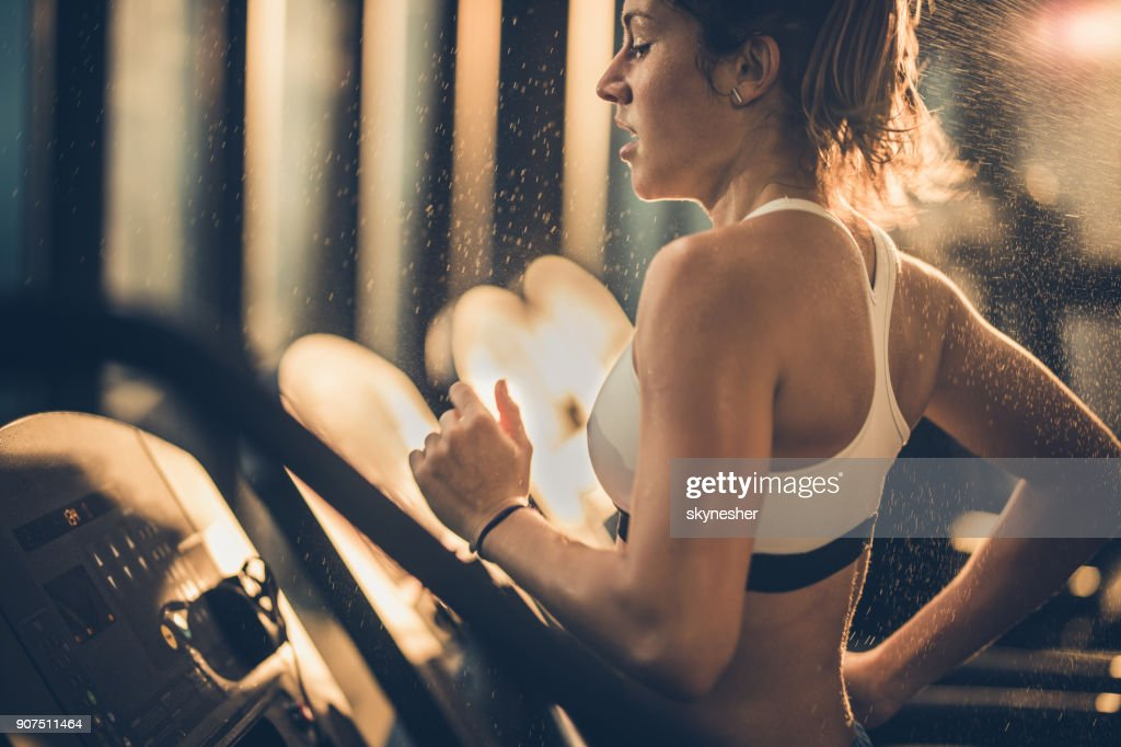 Sweaty woman running on treadmill during sports training in a gym. : Stock Photo