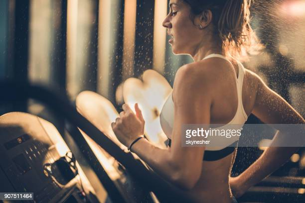 Sweaty woman running on treadmill during sports training in a gym.