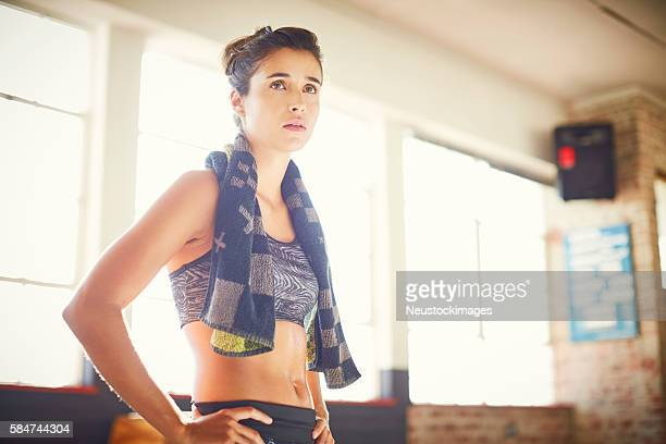 Sweaty woman with hands on hip looking away in gym