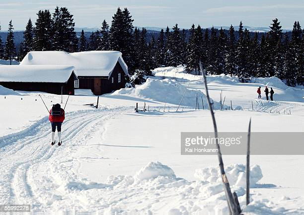 Sweden, cross country skier approaching snow-covered cabins
